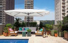 """A área da piscina ganhou um living no projeto do paisagista Gilberto Elkis. """"Queríamos uma área de sombra para ler ou tomar um aperitivo com os amigos"""", diz a moradora Valéria Beraldin. O espaço tem amplo ombrelone, sofá e poltronas com almofadas"""
