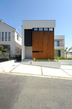 シンプルな外壁と、印象的な濃い木材のコントラストが美しい
