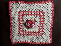 Capa para almofada em crochê feita com barbante cru e rosa.