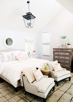Master bedroom with white walls, white bedding, beige bed frame, beige chairs, patterned dresser, light wooden coffee table, light pink patterned pillows, beige and black checkered rug, and glass and black light fixture