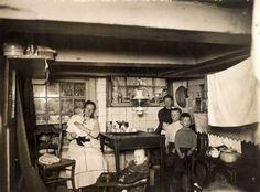 Woonomstandigheden, krotten Nederland. Kelderwoning in de Nieuwe Spiegelstraat te Amsterdam, Nederland 1914. In dit achtervertrek woont een gezin, de familie Rol, bestaand uit man, vrouw en zes kinderen. Het is het enige vertrek voor dit gezin. Bij het kelderraam poseren de moeder en haar zes kinderen rond de tafel, waarboven de olielamp brandt. Het kelderraampje laat slechts flauw daglicht door. Rechts staat een fornuis. De foto is genomen ten behoeve van het artikel in Het Leven, De ...