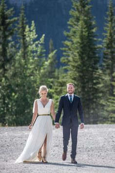 An elegant grecian style wedding dress with gold waistband, v neck and slit in the leg, with flat gold shoes perfect for an outdoor summer mountain wedding. Photo by one-edition.ca