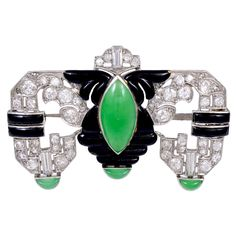 "Gorgeous platinum, diamond, jade and enamel Art Deco brooch. Approximately 2.75 cts of G-H color, VS clarity diamonds adorn this juicy pin. It is approx 1.75"" X 1"", but packs a powerful punch with the apple green jade center and tips play against the black enamel frame and sparkling diamonds. Enamel is on 18K yellow gold. All original from the 1930s."