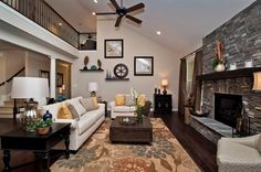 Living room with a fireplace, dark wood floors and high ceilings.