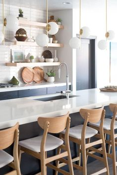 DIY warm modern kitchen with beautiful floating shelves, modern brass lighting and white handmade subway tile. See more on vintagerevivals.com