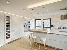 Mittelpunkt der weißen Küche: der gemütliche Tresen mit Barhockern. Mehr zum Projekt auf roomido.com #roomido