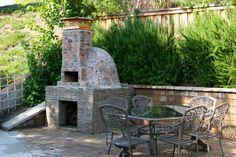 Wood Fired Pizza Oven... I like it incorporating the retaining wall with screen plants