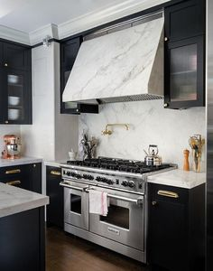 Chic black kitchen features black shaker cabinets adorned with polished brass pulls paired with white marble countertops and white marble slab backsplash.