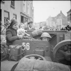 The driver of a Universal carrier, Private H Smith of 'B' Company, 1/4 King's Own Yorkshire Light Infantry, makes friends with Dutch civilians - and a small dog - during the liberation of Roosendaal, The Netherlands, 30 October 1944.