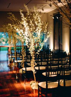Pews decoration inspiration: artificial cherry blossoms and greenery in mason jars on the ground next to the pew.