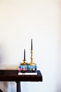 Stacked books on console table with brass candlesticks