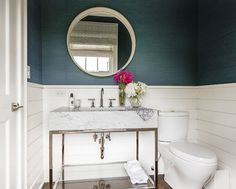 Powder room boasts peacock blue grasscloth on upper walls and shiplap on lower walls lined with a white convex mirror and a marble washstand.