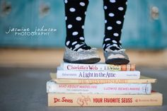 *sort of* what I had in mind for photo on a stack of books. maybe a closeup like this with her favorite titles, and a pull-back of us holding her hands (maybe us from the neck down as a crop) while she stands on the books.