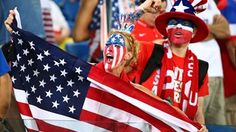 A United States fan cheers while holding an American flag