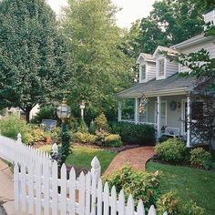White Cape Cod house with picket fence and brick walkway  BHG