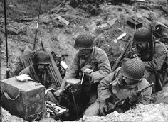 Soldiers are accompanied by a Navajo code talker (seen with the walkie talkie) in June 1944.