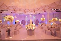 Soft lighting in pink and purple on the draping, and pinspots on the tables