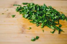 step-by-step-recipe-finely-chopped-fresh-basil-leaves-on-a-wooden-board-seen-in-extreme-close-up