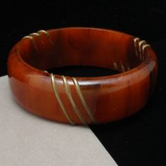 "Tortoiseshell Bakelite bangle bracelet with brass wire insets. Condition is good to very good. There are no marks or hallmarks. This bracelet has a 7"" circumference."