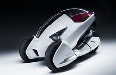 Honda 3R-C Enclosed Three Wheel Scooter    This Honda concept enclosed trike is a scooter geared toward tackling the transportation problem in ever more crowded cities. It is a fully electric scooter, seats one passenger, and the windshield tilts forward to allow the rider to exit the vehicle.