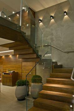 baranda en paneles de vidrio barral de acero pulido sobre pared. Escalera en madera con una excelente iluminacion