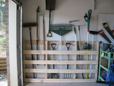 Wood pallet rack for garden tools in garage