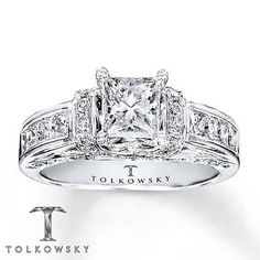 The center Tolkowsky modern princess-cut diamond is bordered with round diamonds on either side of the white gold band.