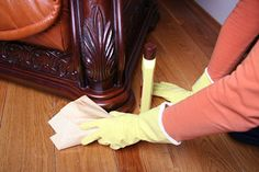 cleaning a wooden sofa leg with furniture cleaner