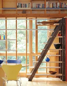 The alternating tread staircase, made from oak and maple, attaches to the side of a built-in refrigerator. It comes in handy as a way to reach cookbooks, which are shelved on the kitchen side of the loft space.