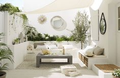 White patio, built in bench, planters, shade