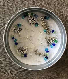 6 wine glass charms in a tin case