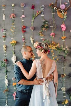 This creative couple relished an intimate embrace in front of a wall trimmed with numerous stems of blooms. | Photographer: Liesl le Roux Photography
