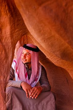Bedouin man wearing traditional dress which consists of a long robe, known locally as a dish-dash or jallabiya, and the plain or checked headscarf, known locally as the hattah, sat amongst the vast sandstone jebels or cliffs of Wadi Rum National Reserve, which is also known as The Valley of the Moon.