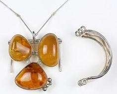 Amber, silver, convertible jewelry suite featuring (3) irregular shaped amber cabochons measuring approximately 45 x 37 x 15 mm, (one is cracked) each are