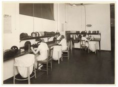 Women cleaning, repairing and rewinding films. Undated. Photographed by Sam Hood. Wearing visors and white dresses. From the collection of the State Library of New South Wales.