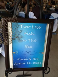 Two Less Fish in The Sea sign at entrance of beach themed wedding