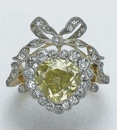 PLATINUM, GOLD, FANCY COLOURED DIAMOND AND NEAR COLOURLESS DIAMOND RING, CIRCA 1890. One heart-shaped diamond, with GIA report stating the diamond is 1.92 cts, Natural Fancy Intense Yellow.