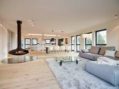 meubles blanc et bois clair, canapé d'angle gris perle, tapis shaggy et table basse sur roulettes