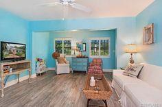 Bright blue beachy coastal family room - wood floors and white furniture.  Olde Naples, FL