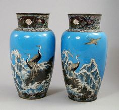 A pair of Japanese enamel vases, Meiji period, decorated with crane perching on rocks amidst waves, 30.5cm. high