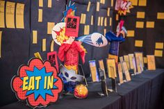 Pop Art signs identified each of the auction categories, with masks and other superhero props decorating the tables.