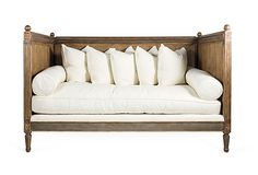 French-style daybed with two off-white bolsters and five cushions.