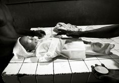 At a funeral home in Anuradhpuraq, North Sri Lanka, funeral workers care a child victim of the June 15 bus attack to prepare for mass burial. Sri Lanka, June 16,2006 Q. Sakamaki Photography
