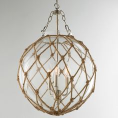 """Rope Net Glass Sphere Chandelier Knot your average chandelier! Rope in a lattice net pattern wraps a clear glass globe with chrome shackles and chain and a cluster of 3 lights inside for a nautical necessity. 3x40 watts candle sockets. (24""""Hx16""""W)"""