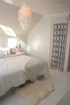 Floor to ceiling painted wood paneling in a neutral light blue and off-white for attic guest bedroom.