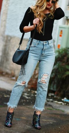 Edgy winter outfit with off the shoulder bodysuit. high waisted distressed jeans, and brocade booties