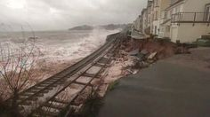 Parts of Britain have been hit by a storm which destroyed a stretch of railway, forced people from their homes and left thousands without power.