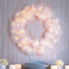 "A delicate-looking wreath that creates the magical effect of candles flickering in the snow is easy to make and surprisingly sturdy. Wreath frames are strung with twinkling lights that are nestled in frothy, doilylike paper bouquet holders known as ""Biedermeiermanschetten."""