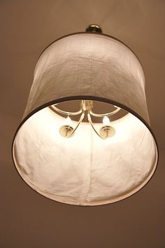 Smart...she covered her hated existing chandelier with a homemade fabric shade