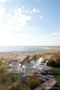 A New England home by the sea with adirondack chairs overlooking the beach.
